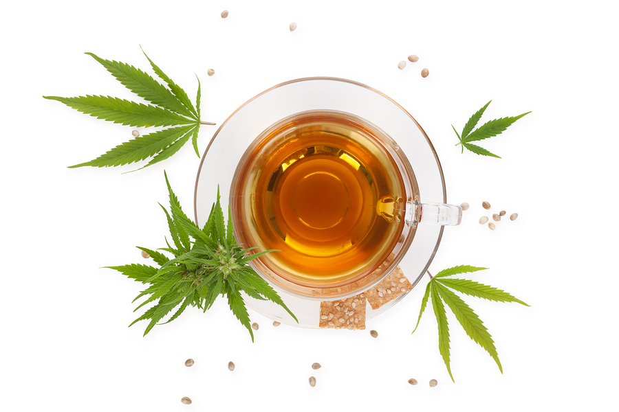 Cannabis tea with crackers from above with cannabis plant and leaves isolated on white background. Alternative medicine medical cannabis natural remedy.